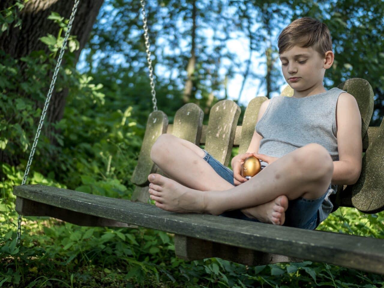 Junge sitzend auf Schaukel mit Klangei gold
